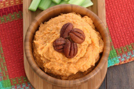 Sweet Potato Bean Dip in a wood bowl on a wood serving platter with carrot and celery sticks