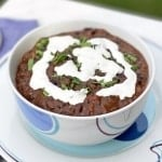 Black Bean Soup with Cilantro-Lime Cream in a white bowl on a white plate with a blue napkin and spoon next to it