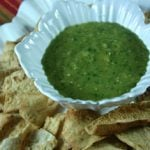 Roasted Tomatillo Salsa in a white bowl surrounded by tortilla chips