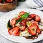 Mozzarella, strawberries, and mint drizzle of a white plate