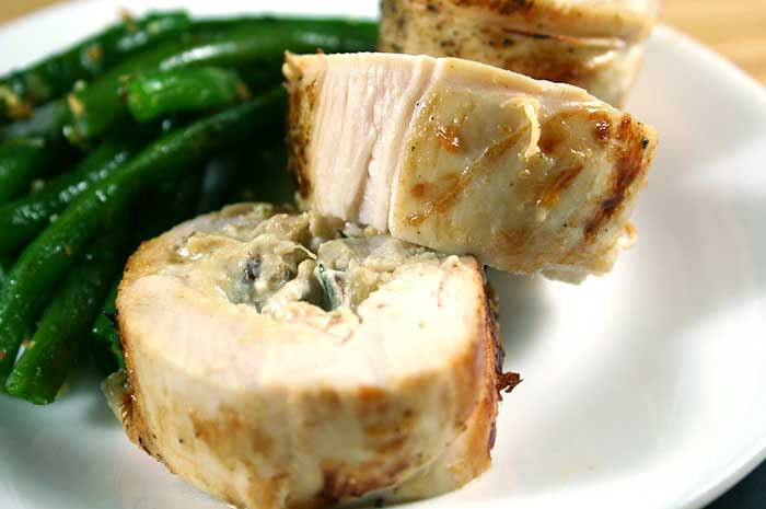 Chicken Roulade with Goat Cheese and Dates on a white plate with green beans