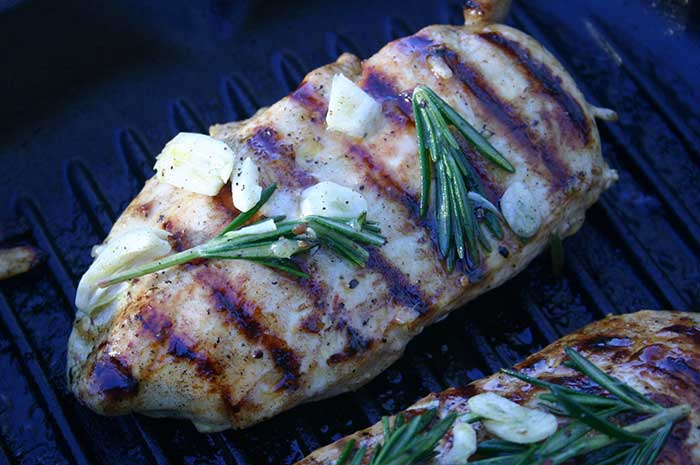 Grilled Marinated Chicken Breast with garlic and rosemary on a grill pan