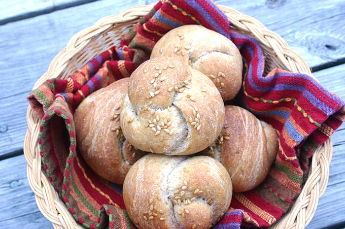 Whole Wheat Flax Dinner Rolls in a bread basket with a colorful cloth napkin