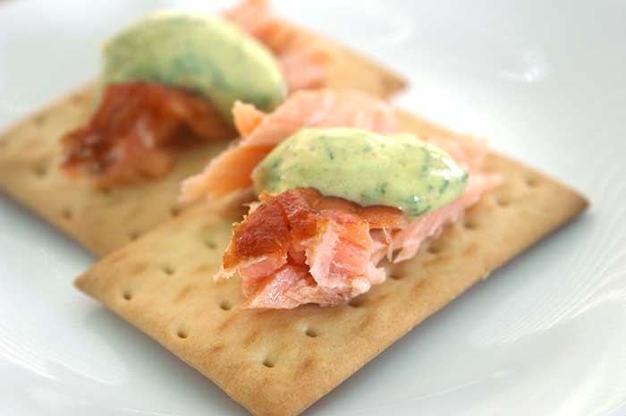 Smoked Salmon with Dill-Mustard Sauce on crackers on a white plate
