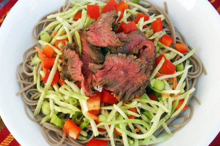 Asian steak salad in a white bowl topped with sliced green onion