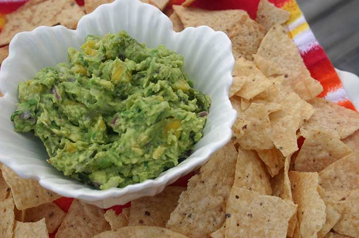 Guacamole in a white dish with tortilla chips