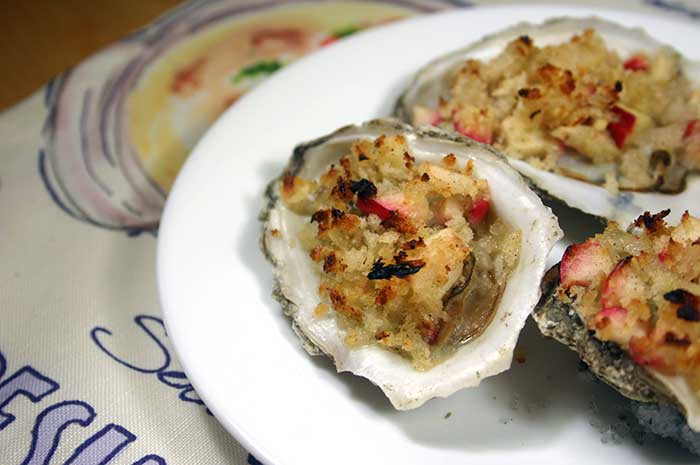 Several Baked Oysters and Apples on a white serving plate