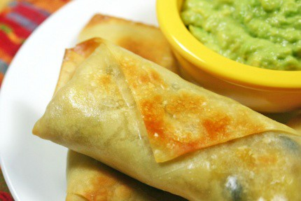 Southwestern Egg Rolls stacked on a white plate next to a yellow ramekin of guacamole