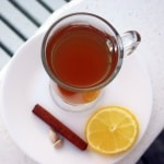 Spiced Ginger Tea in a glass mug on a white plate next to a slice of lemon, a cinnamon stick, and cardamom pods