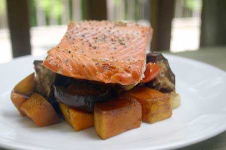 Salmon served over roasted vegetables on a white plate