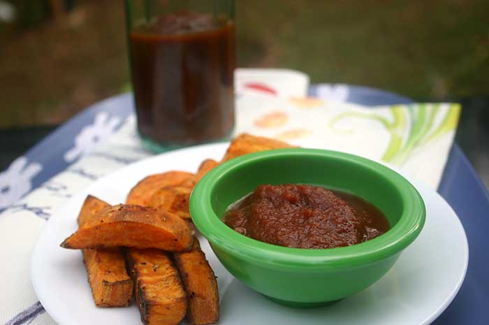 Quick and Easy Homemade Ketchup in a green ramekin on a white plate next to sweet potato fries