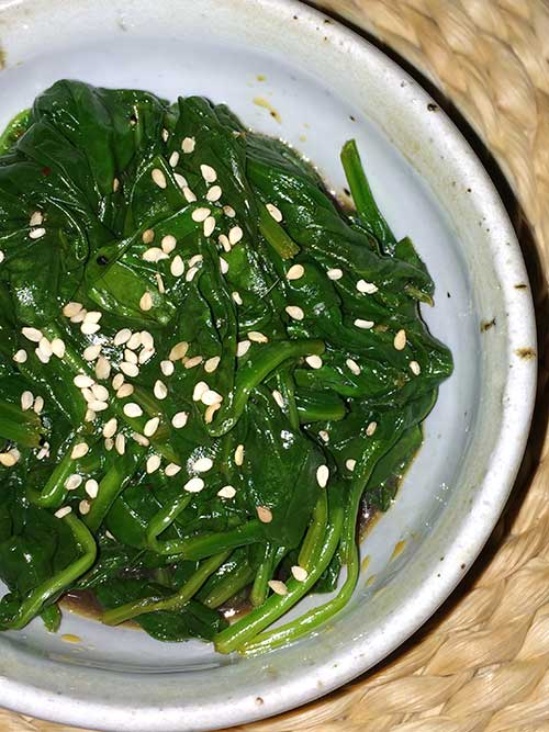 close-up of Szechuan Spinach in a white bowl