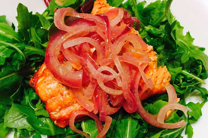 Overhead view of broiled Salmon with Onion Marmalade over Greens on a white plate