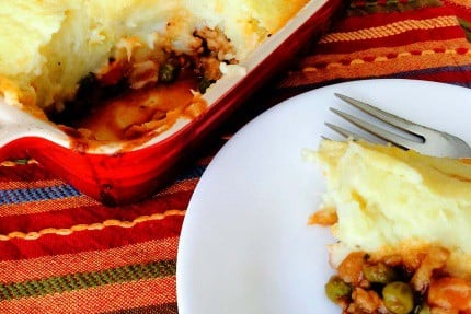 A slice of shepherd's pie on a white plate next to the full pie in a baking dish