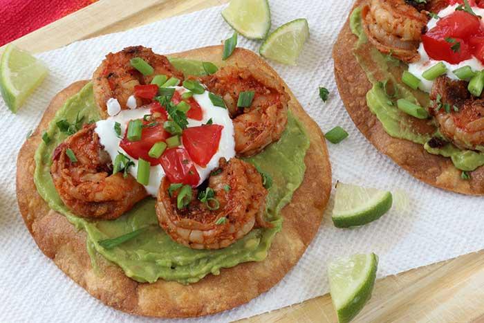 Two Shrimp Avocado Tostadas served with lime wedges