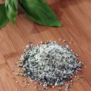 A pile of Basil Salt on a wooden cutting board next to basil leaves