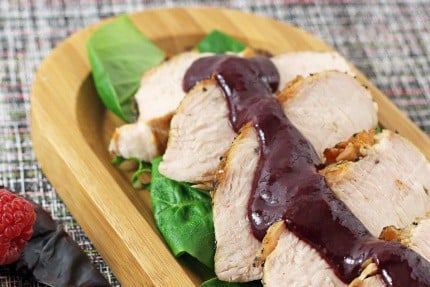 Grilled Turkey Tenderloin with Berry Chipotle Sauce cut into slices and served over greens on a platter