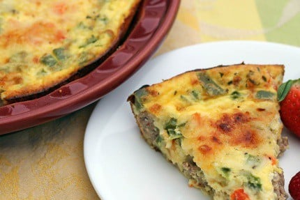 Crustless Quiche with Italian Turkey Sausage and Peppers in a baking dish with one slice removed to a plate