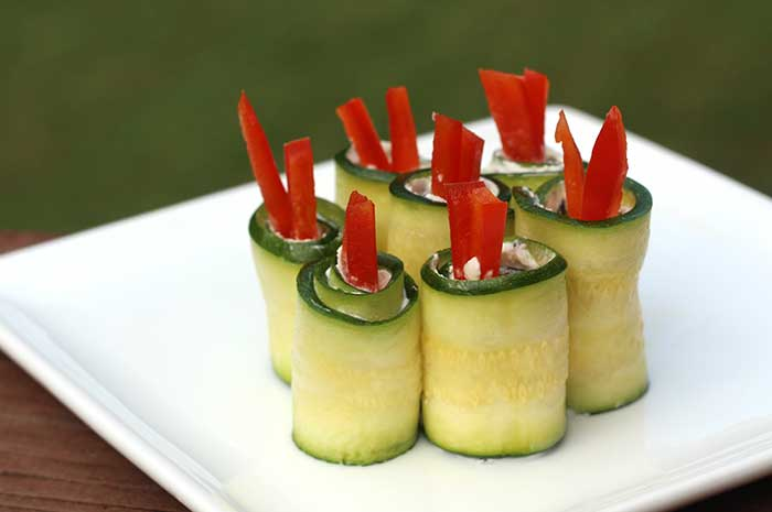 7 Zucchini Roll-Ups with Goat Cheese and Peppers on a white plate