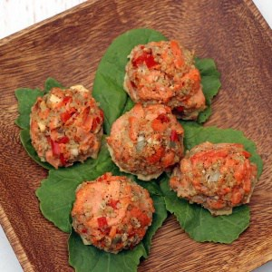 Salmon Meatballs with Quinoa on a wooden plate with leaves under each meatball