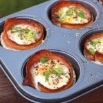 Bacon Egg Cups in a muffin tin topped with chopped scallion