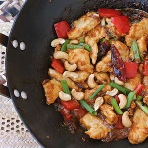 Kung Pao dish with chicken, chilis, green onion, and cashews in a skillet