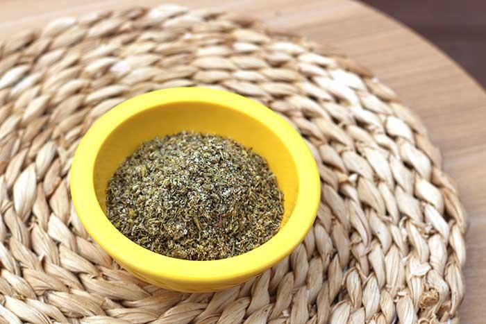 Low-Sodium Zaatar Seasoning in a yellow ramekin on a decorative placemat