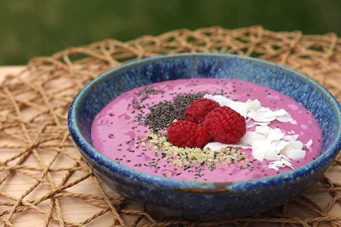 Berry Smoothie Bowl topped with chia seeds, hemp hearts, raspberries, and coconut flakes in a blue bowl
