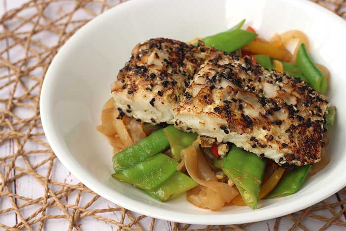 Sesame Coconut-Crusted Halibut served over vegetables in a white bowl