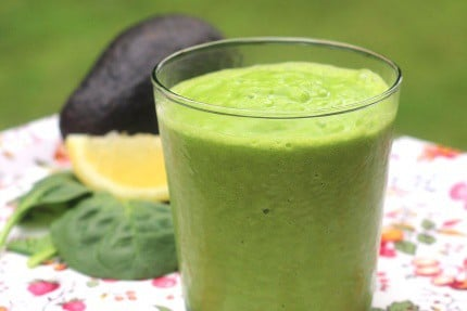 Avocado Smoothie with Leafy Greens in a glass with spinach, lemon, and an avocado in the background