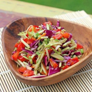 Sesame Broccoli Slaw in a wooden serving bowl on a decorative placemat