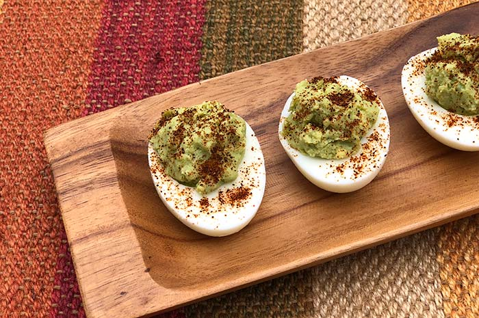 3-Ingredient Guacamole Deviled Eggs seasoned with chili powder on a wood serving tray