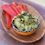 Pear Guacamole with Pistachios in a ramekin on a wooden serving tray with sliced red bell peppers