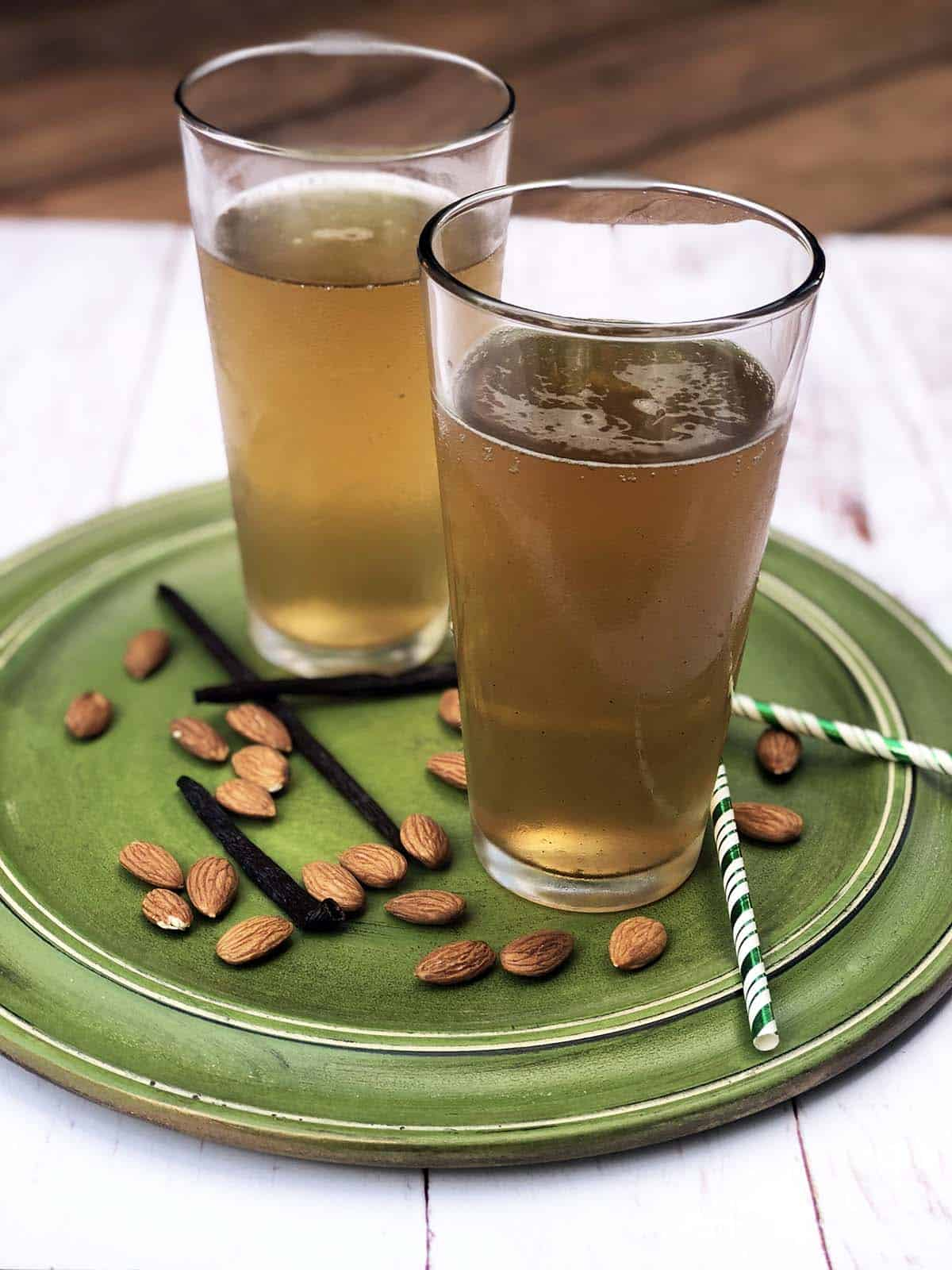 Two glasses of Apple Cider Vinegar Soda on a plate with almonds, vanilla pods, and two straws