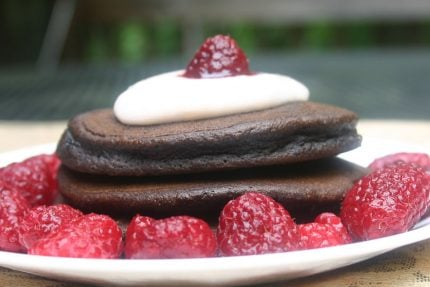 Stack of Brownie Pancakes with berries and whipped cream