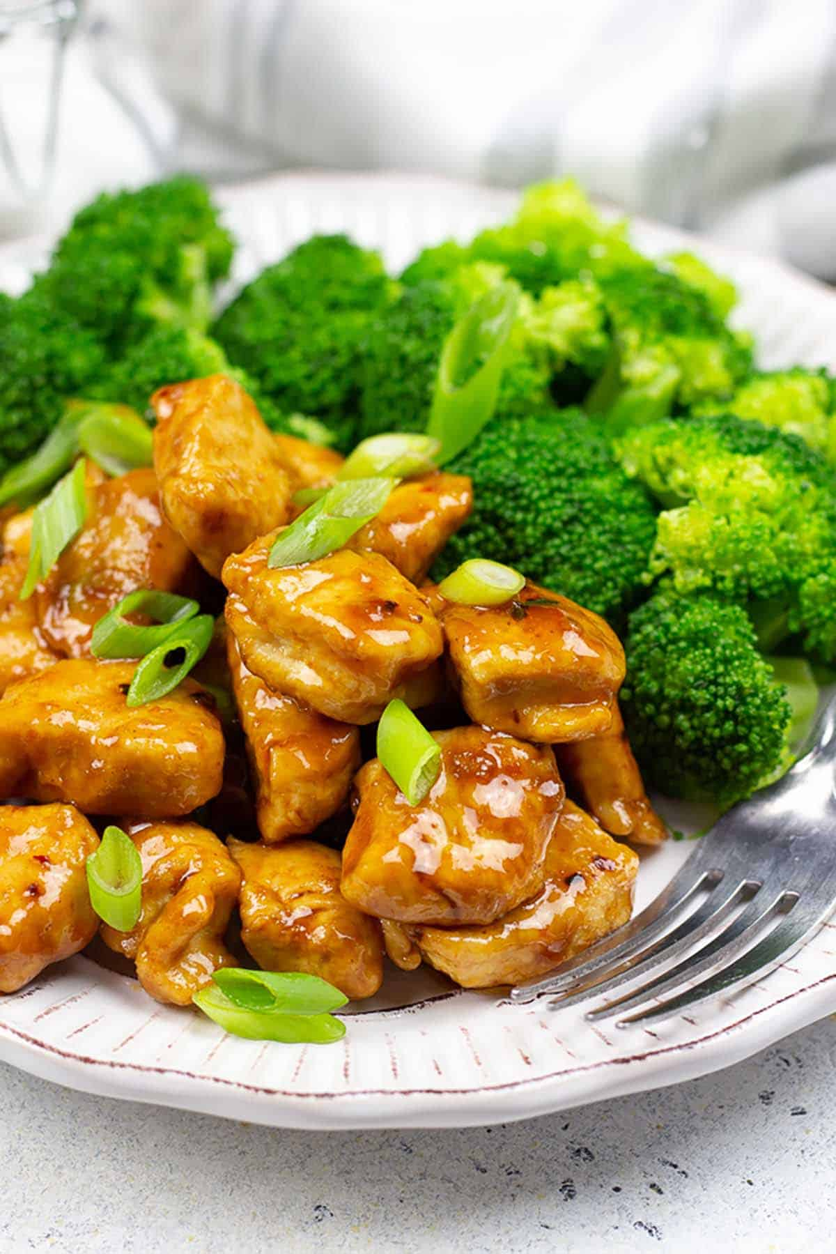 Low-Carb General Tso's Chicken on a plate with steamed broccoli