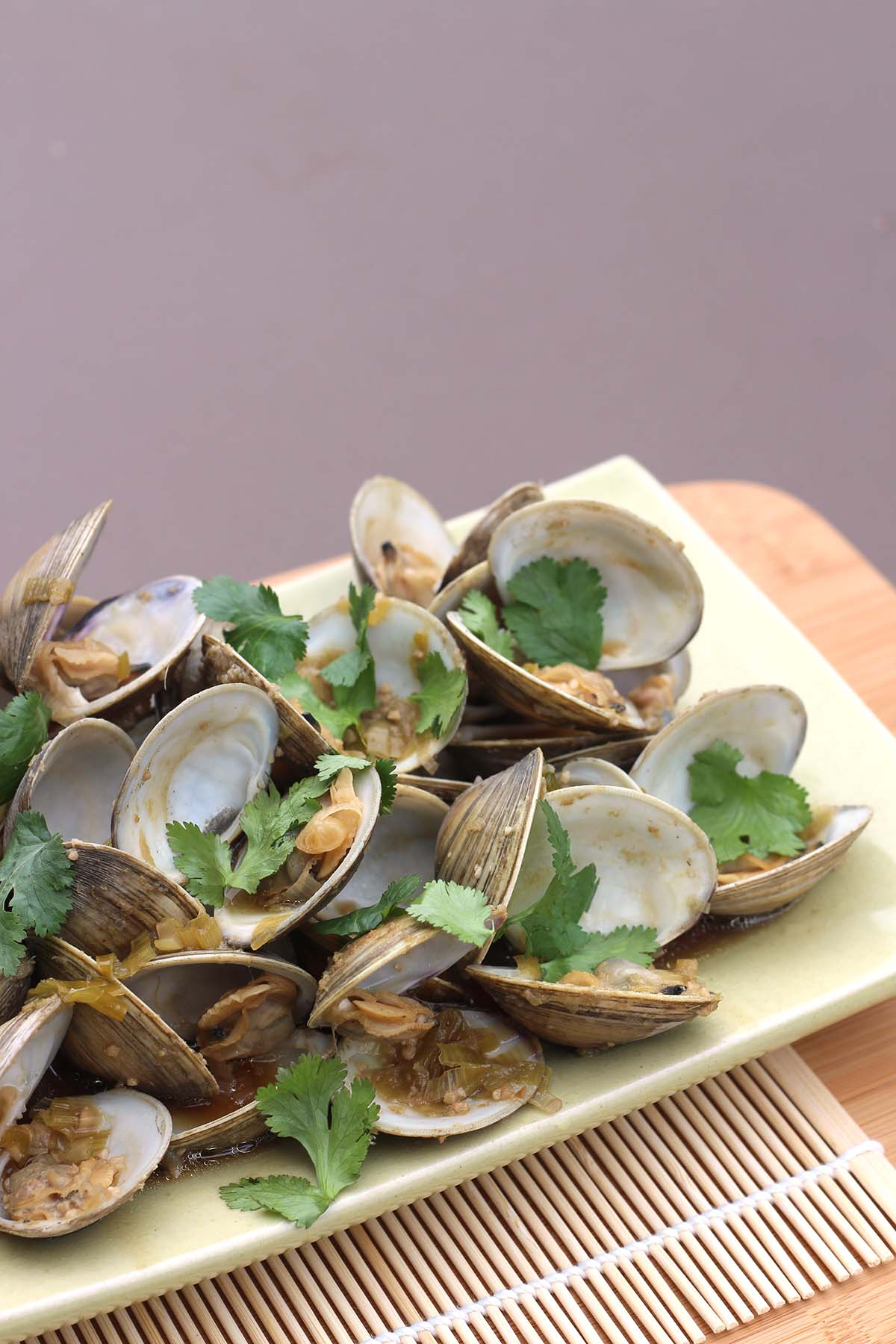 Asian Steamed Clams with Ginger and Garlic on a platter garnished with cilantro