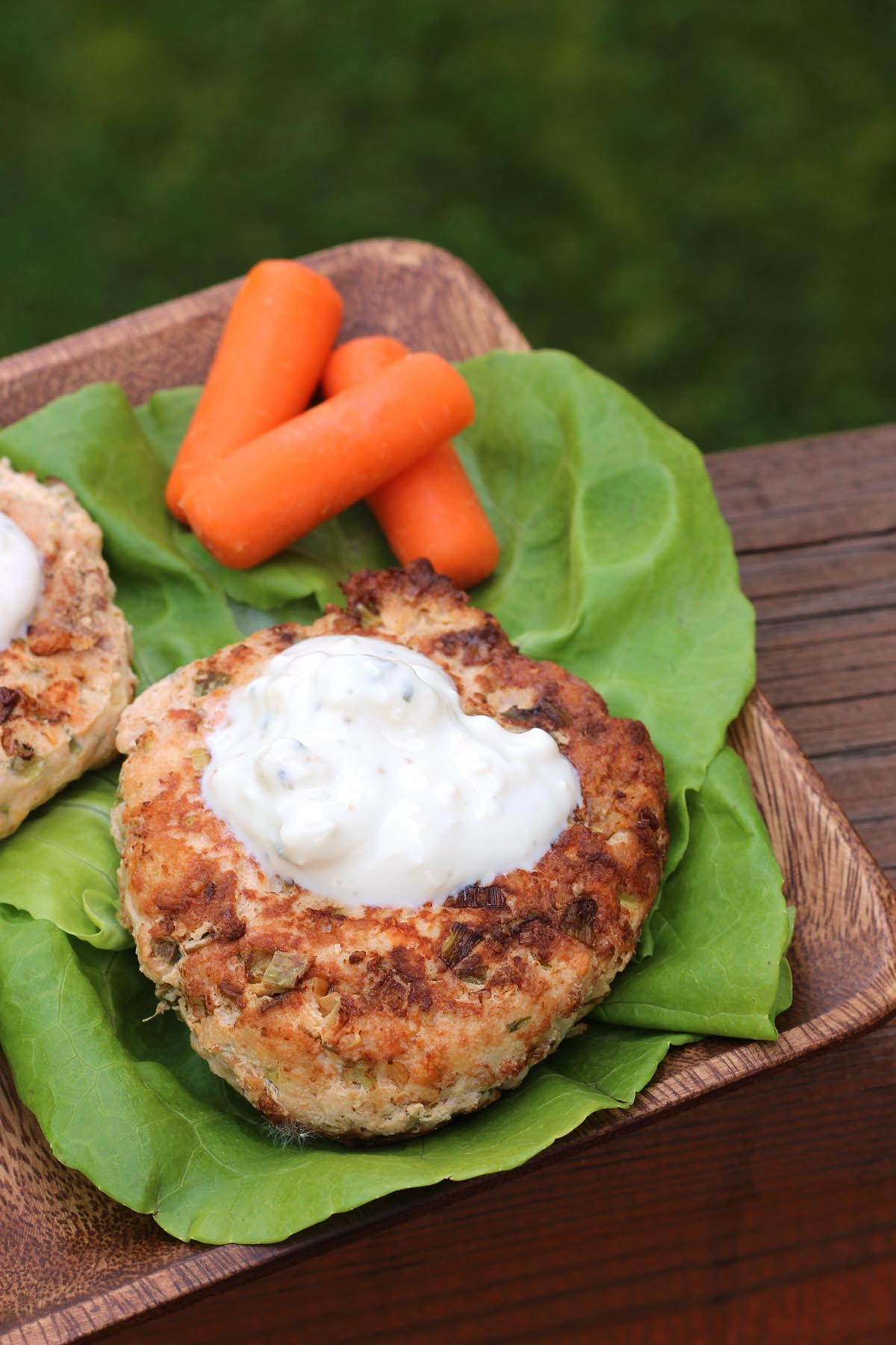 Buffalo Chicken Burgers on a bed of lettuce topped with blue cheese dressing