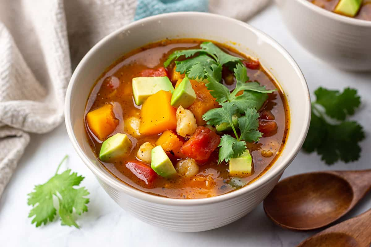 Butternut Squash Posole in a bowl topped with chopped avocado and cilantro