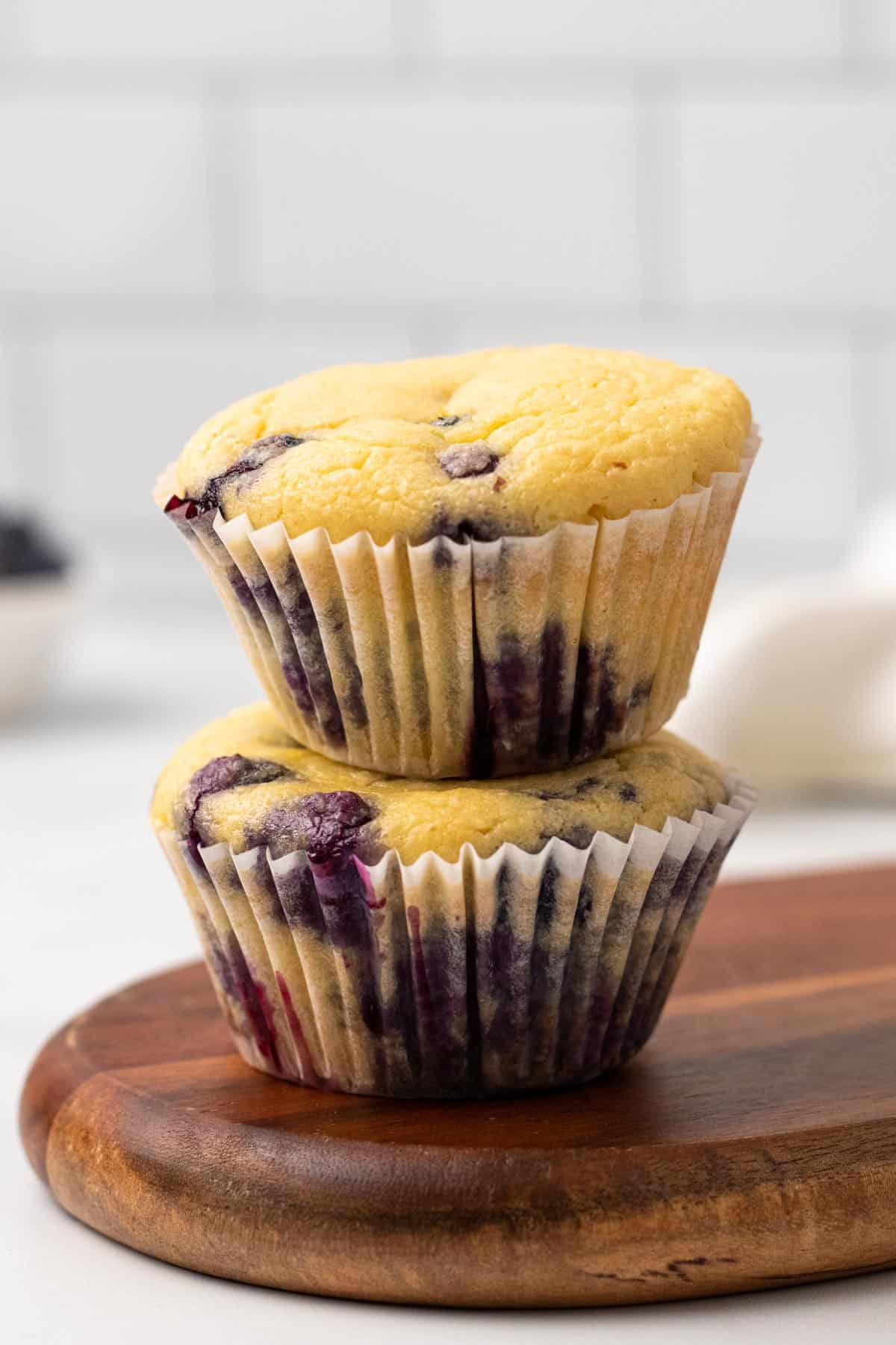 Stack of two Blueberry Muffins (with Coconut Oil) on a wooden cutting board