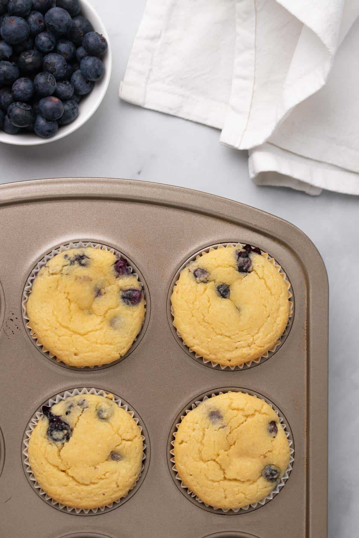 Close-up of blueberry muffins in a pan next to a ramekin of fresh blueberries