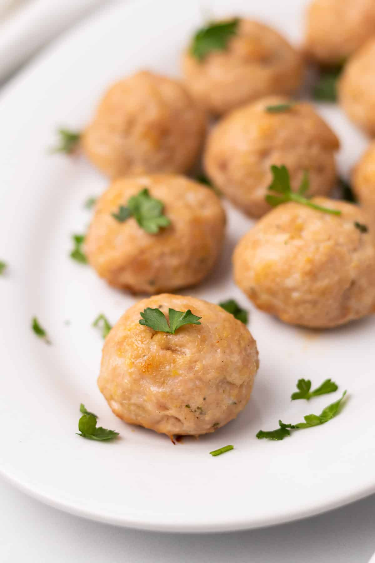 Close-up of chicken meatballs on a white serving platter