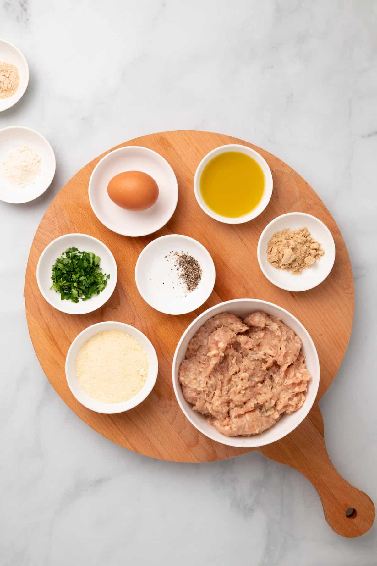 Ingredients for meatballs in separate ramekins and dishes, as seen from above