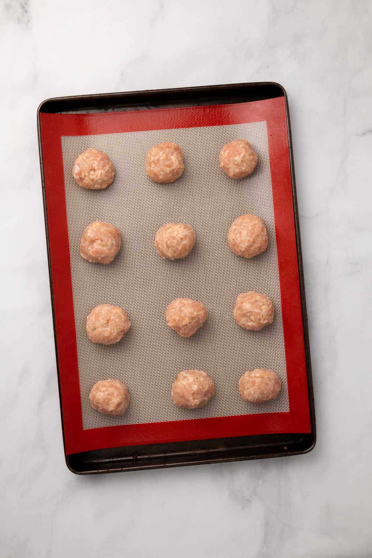 Prepared meatballs on a baking tray, ready to go in the oven
