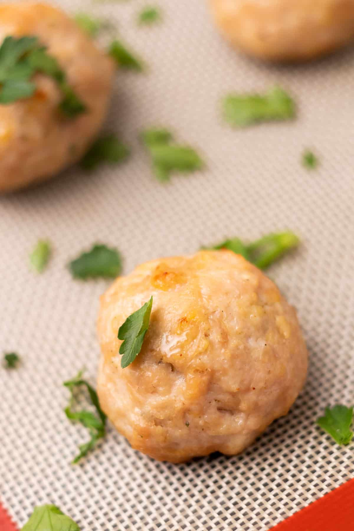 Close-up of meatball on the baking tray, garnished with parsley