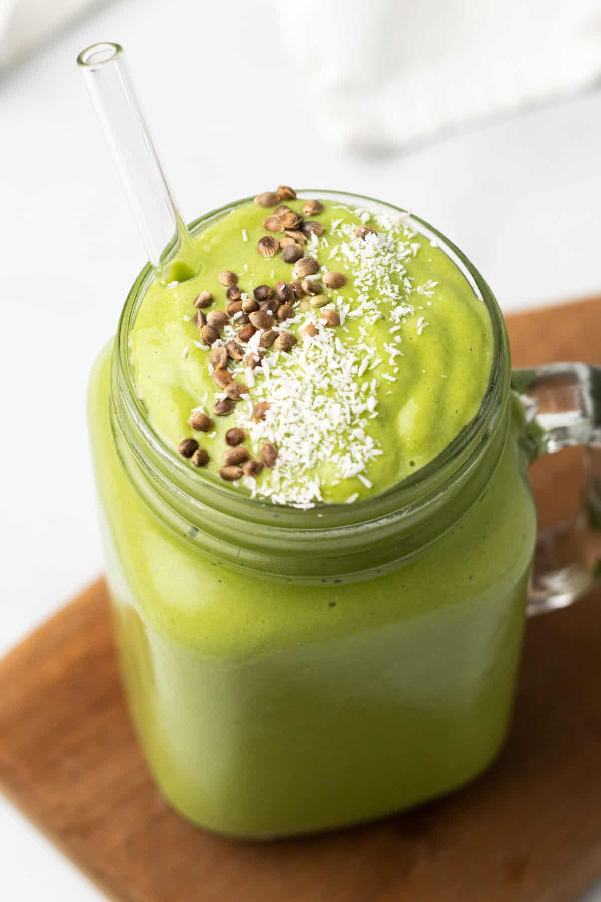 Low-Carb Green Smoothie in a glass jar with a glass straw and topped with shredded coconut and flax seeds