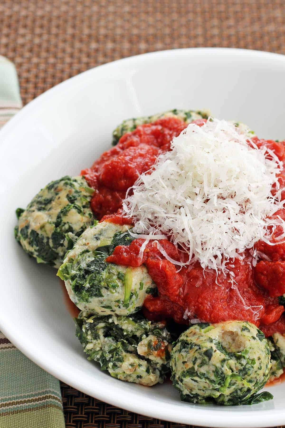 Spinach Dumplings in a white bowl topped with tomato sauce and parmesan