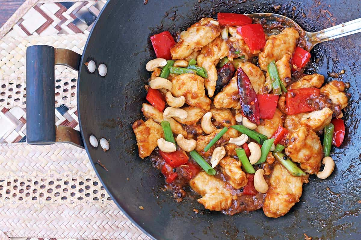 Kung Pao dish with chicken, chilis, green onion, and cashews in a wok