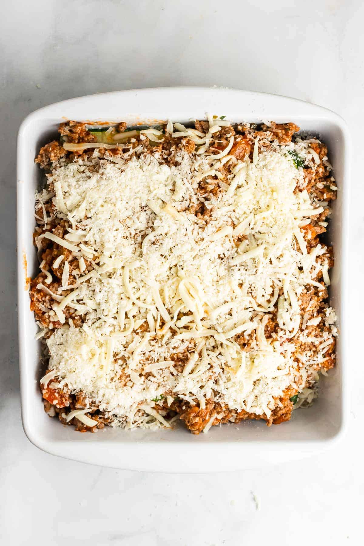Assembled lasagna topped with Parmesan cheese, ready to go into the oven