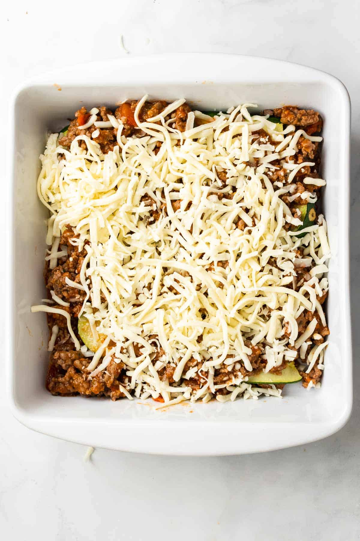 Assembling the lasagna with mozzarella cheese over zucchini slices and the ground beef sauce in a baking pan, as seen from above